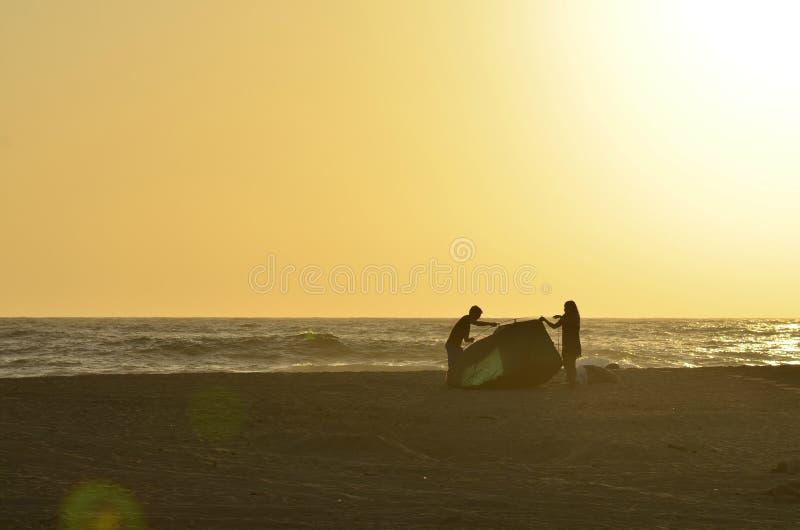 投入帐篷的年轻夫妇男人和妇女剪影在热带海滩 免版税图库摄影
