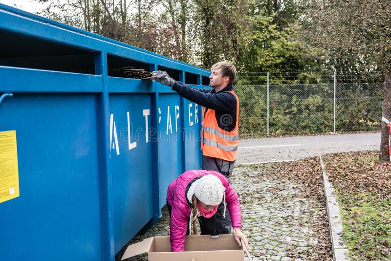 投入废纸的妇女和人在容器在回收中心 免版税库存照片