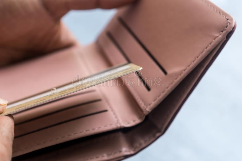 投入或采取或支付与信用卡的年轻商人特写镜头照片在皮革钱包里在白色背景 免版税库存图片