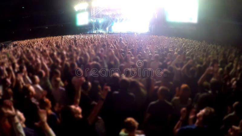 投入手在空气和拍手,爱好者在音乐会的人人群,体育场 免版税库存图片