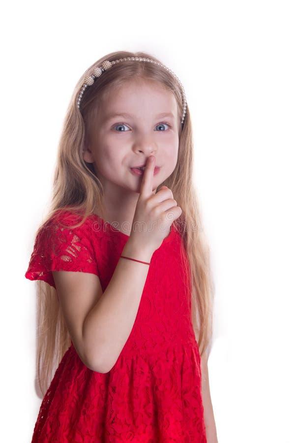 投入手指的红色礼服的说白肤金发的女孩由嘴唇决定嘘 库存图片