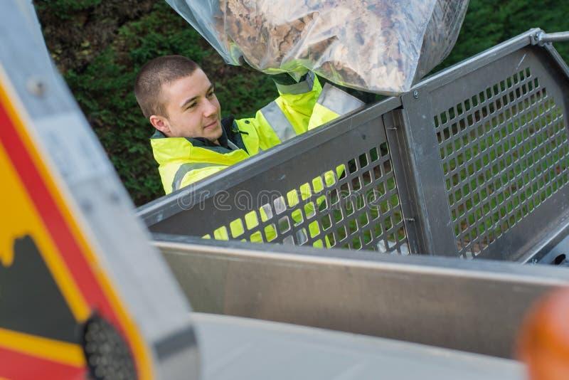 投入收集的叶子的年轻垃圾收集工在卡车 免版税图库摄影