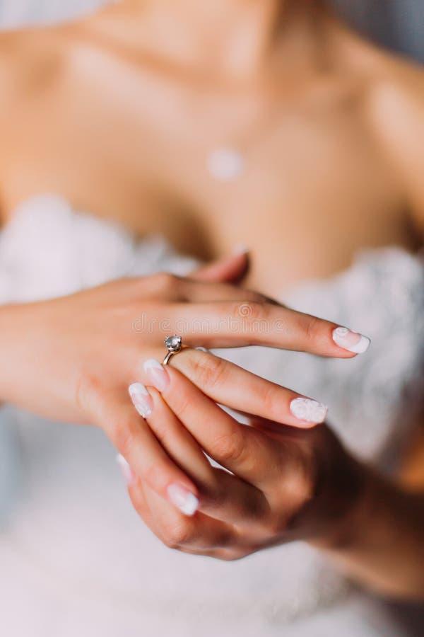 投入昂贵的定婚戒指的白色礼服的美丽的新娘 免版税库存图片