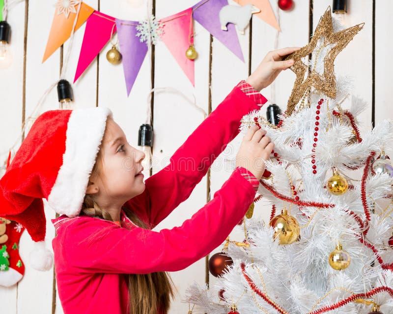 投入星的红色帽子的小女孩在圣诞树顶部 免版税库存照片