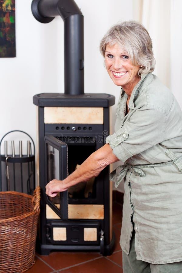 投入木头的资深夫人在火炉 免版税库存照片