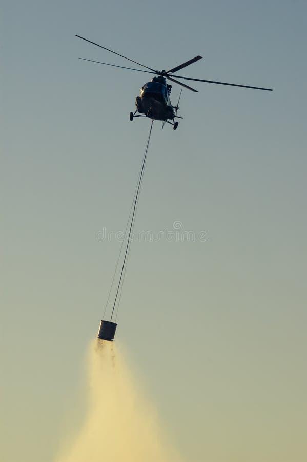 投入森林火灾的军用直升机在Istria克罗地亚在日落 免版税库存图片