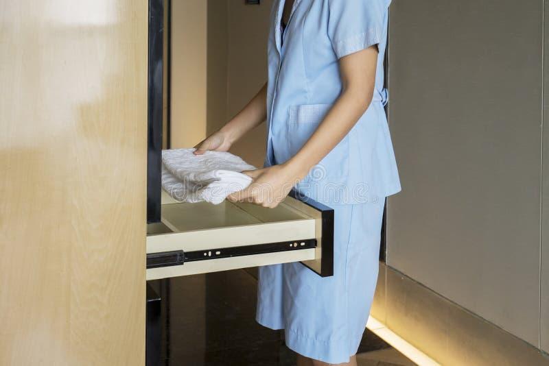 投入毛巾的未知的佣人在抽屉 免版税库存照片