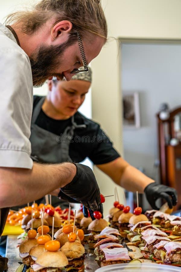 投入汉堡的成份女性和男性厨师在表上的被切的面包传播在黑手套 库存照片