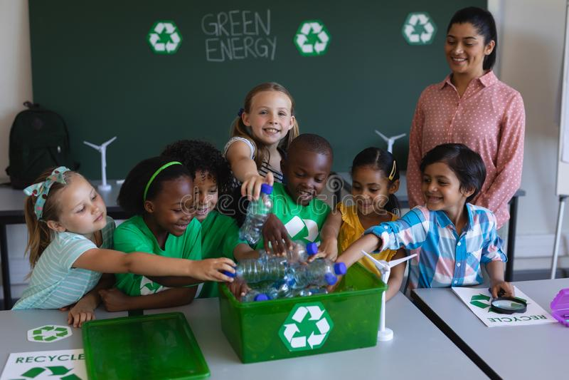 投入瓶的Schoolkids回收容器在书桌在教室 图库摄影