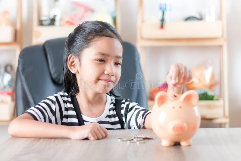 投入的硬币亚裔女孩对存钱罐浅景深精选的焦点在面孔 免版税库存图片