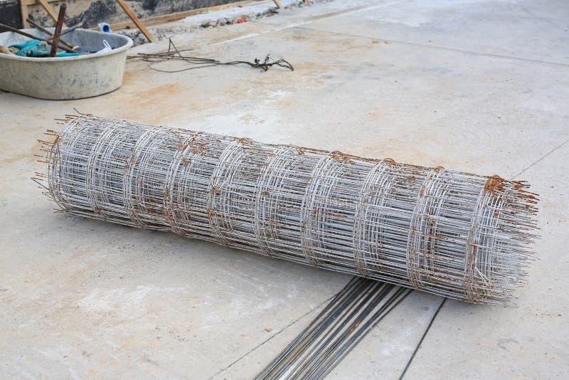 投入的铁丝网钢劳斯堆在地面上 具体建筑的钢被加强的标尺 免版税库存照片