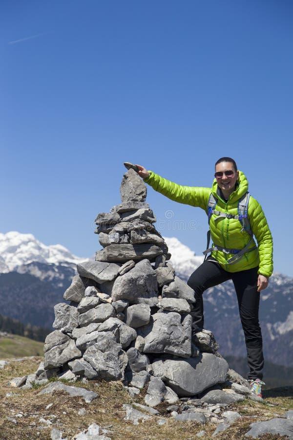 投入石头,在石堆的小岩石的愉快的女孩远足者,高在山 免版税库存图片