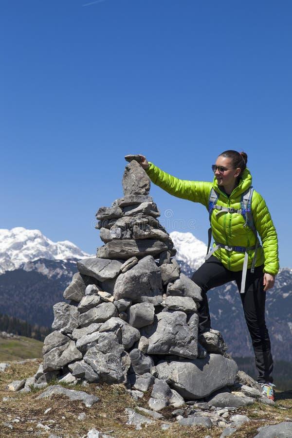 投入石头,在石堆的小岩石的愉快的女孩远足者,高在山 免版税库存照片