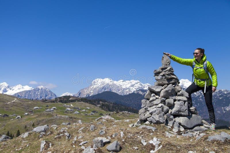 投入石头,在石堆的小岩石的愉快的女孩远足者,高在山 库存照片
