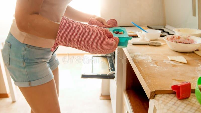 投入硅树脂形式用杯形蛋糕的年轻女人特写镜头照片在热的烤箱 主妇烘烤和烹调在厨房在 库存照片