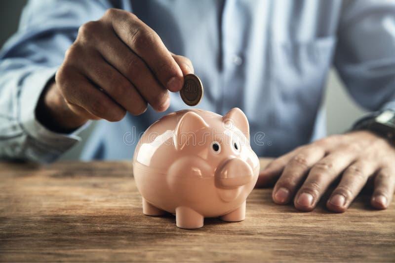 投入硬币的商人在存钱罐中 银行票据贪心放置的节省额 库存照片