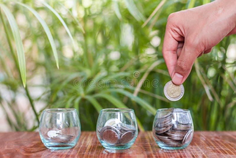 投入硬币的妇女的手在玻璃瓶子, 免版税库存图片
