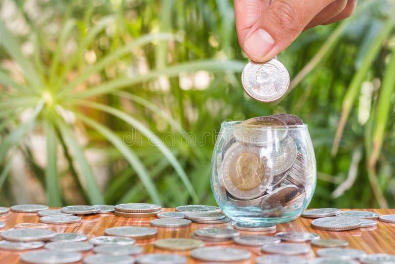 投入硬币的妇女的手在玻璃瓶子 免版税库存图片