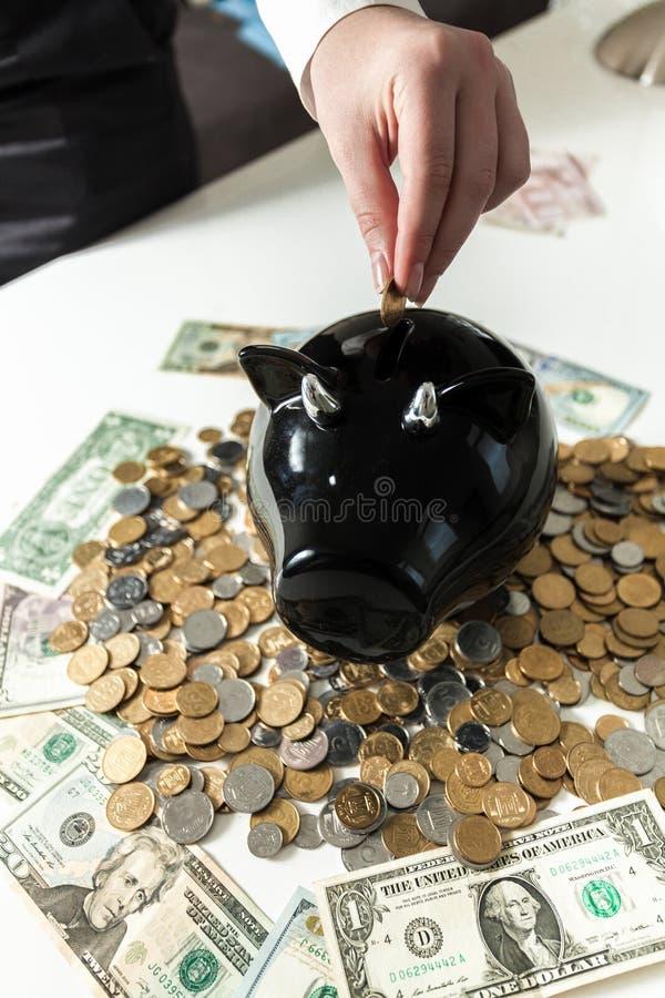 投入硬币的手照片在黑存钱罐中 免版税图库摄影