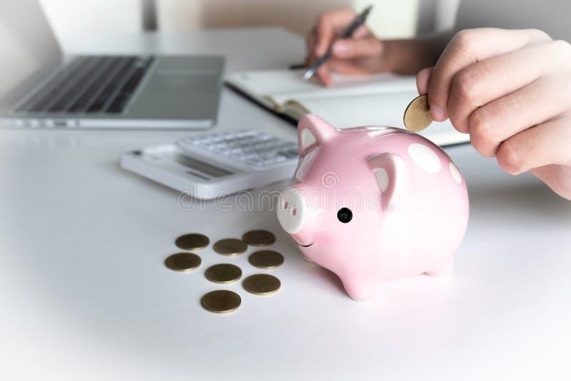 投入硬币的现代妇女在桃红色存钱罐中 免版税库存图片