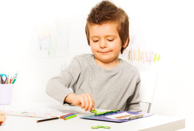 投入硬币的男孩作为刺激行使 免版税库存照片