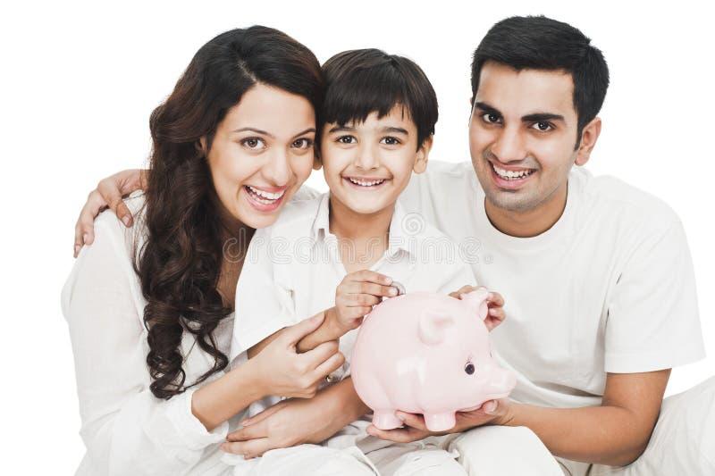 投入硬币的男孩在有他父母微笑的存钱罐中 免版税库存图片