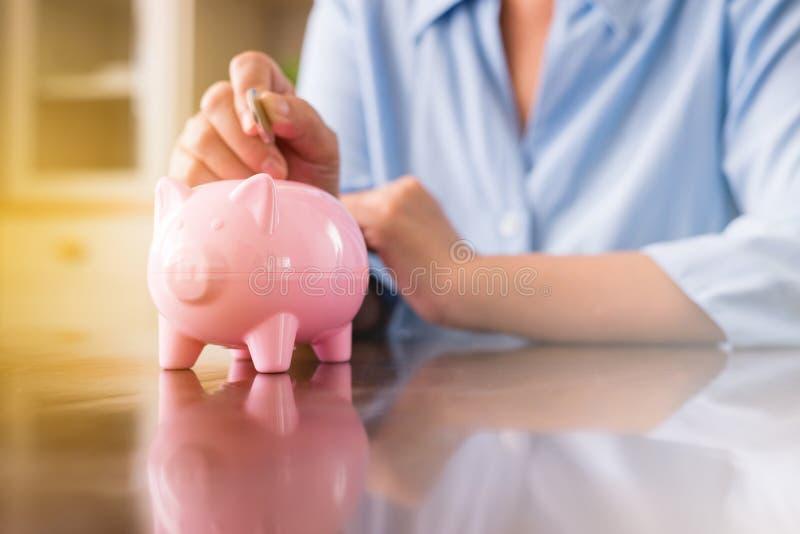 投入硬币的资深手对退休的,攒钱概念,攒钱概念存钱罐 免版税图库摄影