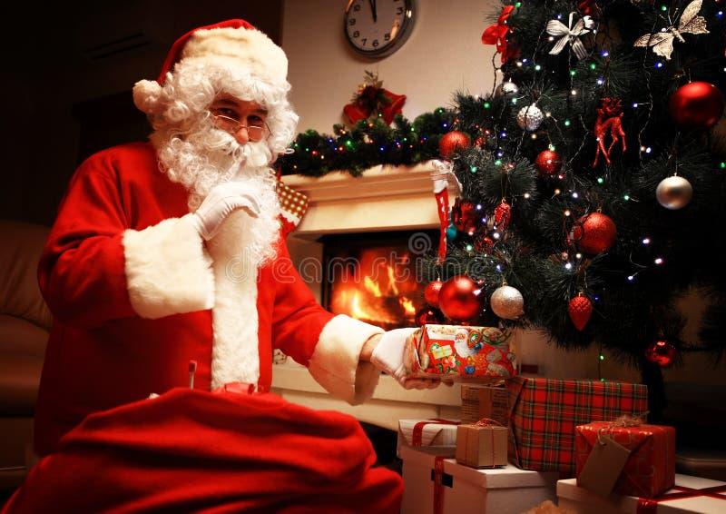 投入礼物盒或礼物的圣诞老人在圣诞树下在前夕晚上 静寂s秘密 不要告诉孩子 Xmas和 库存图片