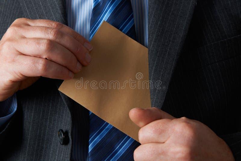 投入简单的布朗信封的商人在夹克口袋 免版税库存照片