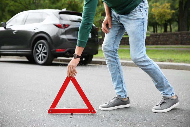 投入紧急刹车标志的人在残破的汽车附近 免版税库存图片