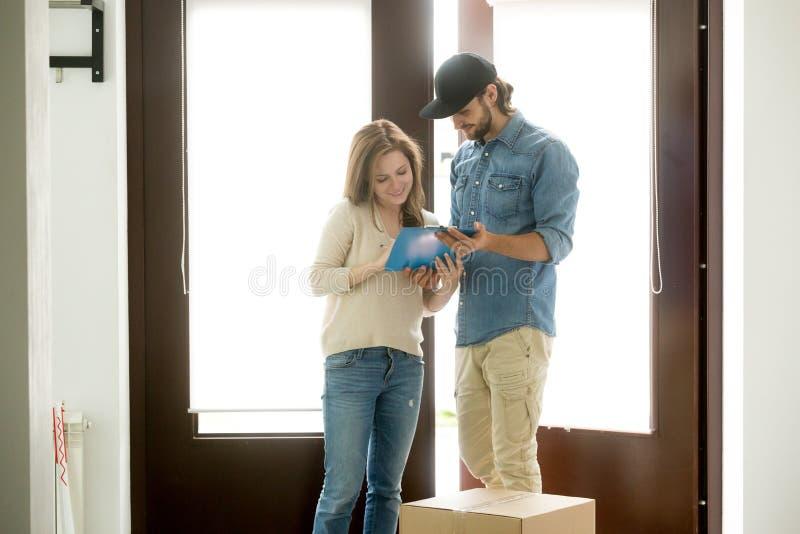 投入署名的妇女接受小包从送货人在ho 免版税库存照片