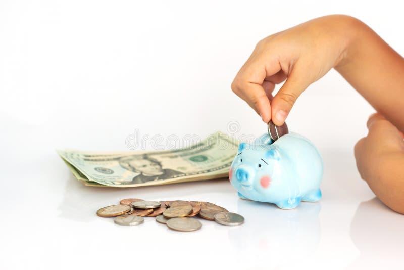 投入美元硬币的亚裔女孩在存钱罐中 免版税库存照片