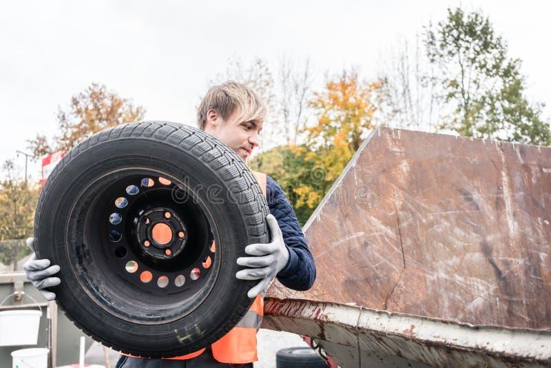 投入老轮胎的人在容器回收中心 免版税库存照片