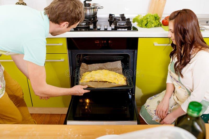 投入苹果的Married微笑的夫妇对烤箱在厨房 免版税库存照片