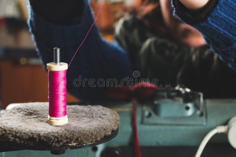 投入螺纹的裁缝在缝纫机 免版税库存照片
