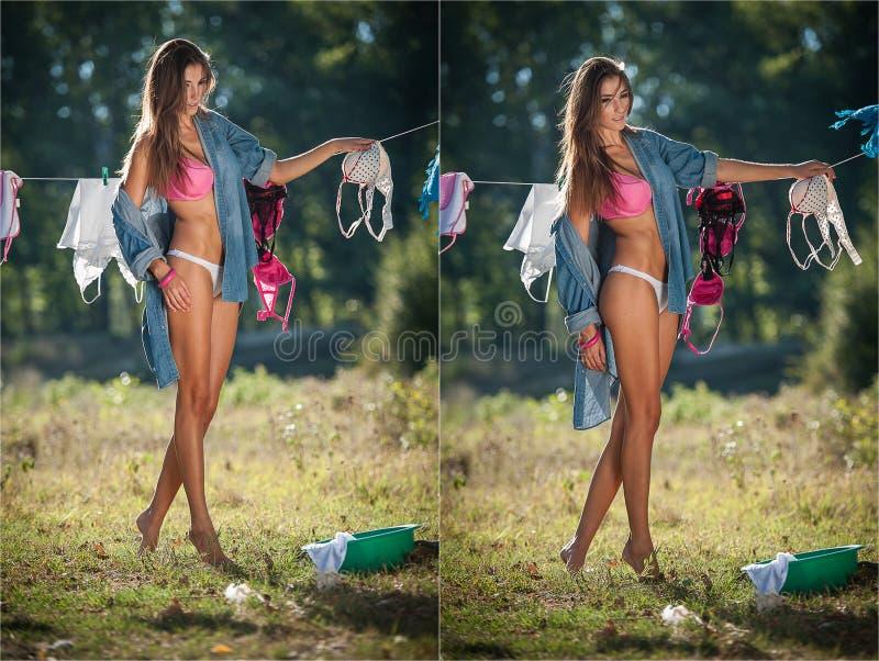 投入衣裳的比基尼泳装和衬衣的性感的深色的妇女烘干在太阳 有投入洗涤物的长的腿的肉欲的年轻女性 免版税图库摄影