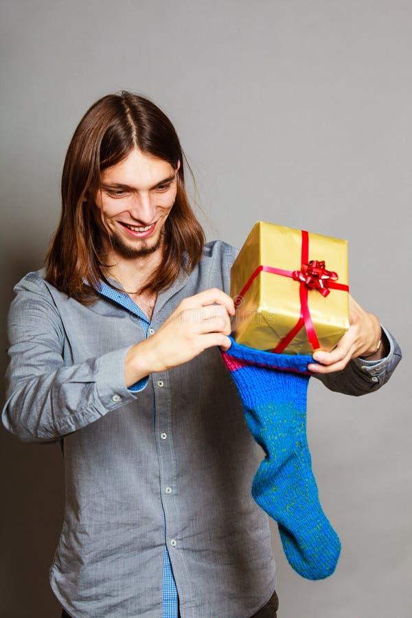 投入被包裹的礼物的人在被编织的圣诞节袜子 免版税库存图片