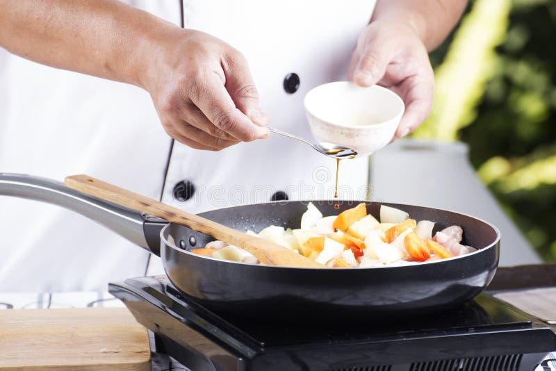 投入调味酱的厨师到烹调的日本por平底锅 免版税库存图片