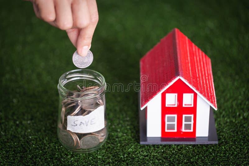 投入金钱与式样房子的手硬币堆;物产投资和房子抵押财政概念 库存照片