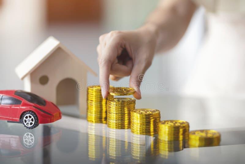投入金钱与木房子和红色汽车抵押,物产投资的妇女手硬币堆财政 购买的攒钱 库存图片