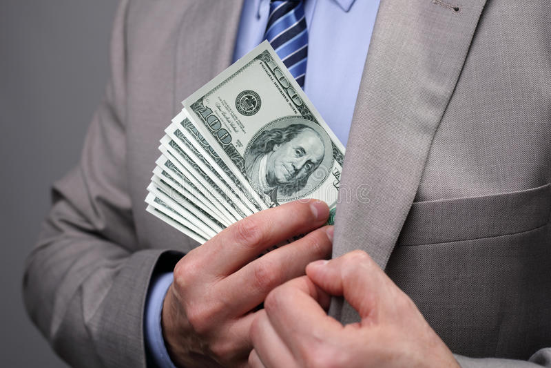 投入金钱的商人在口袋 库存照片