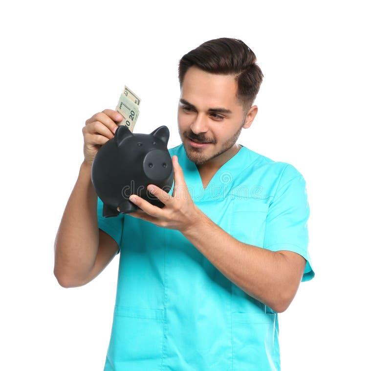 投入金钱的年轻男性医生画象  图库摄影