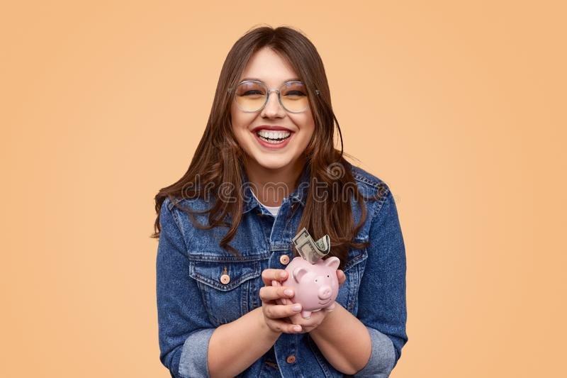 投入金钱的笑的胖的妇女在存钱罐中 库存照片