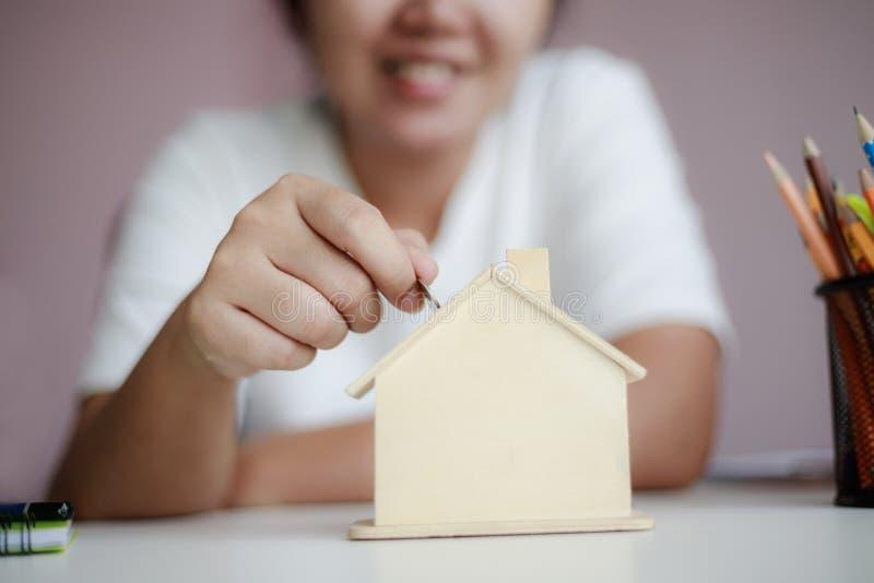 投入金钱硬币的愉快的亚裔妇女对购买的木房子存钱罐隐喻攒钱浅房子精选的焦点 免版税库存图片