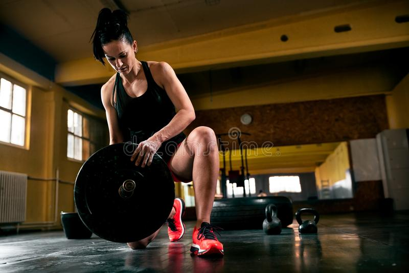 投入锻炼的肌肉少妇大量的重量 免版税图库摄影