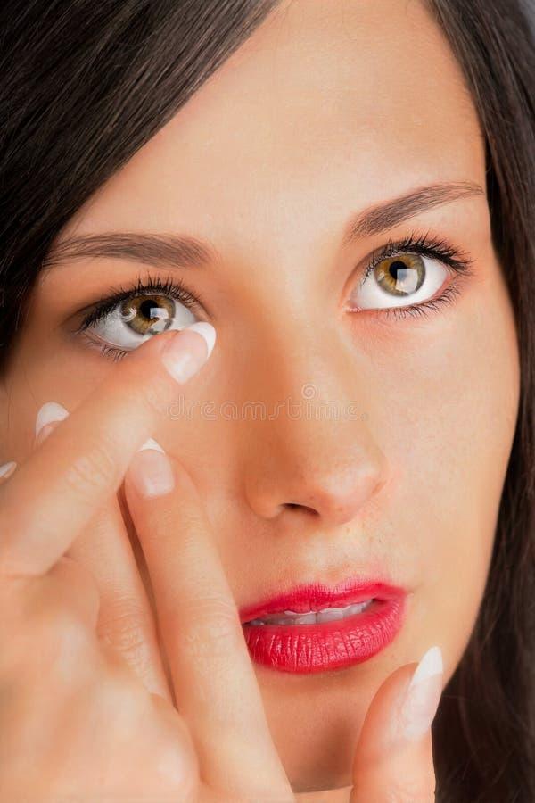 投入隐形眼镜的少妇在她的眼睛 免版税库存图片