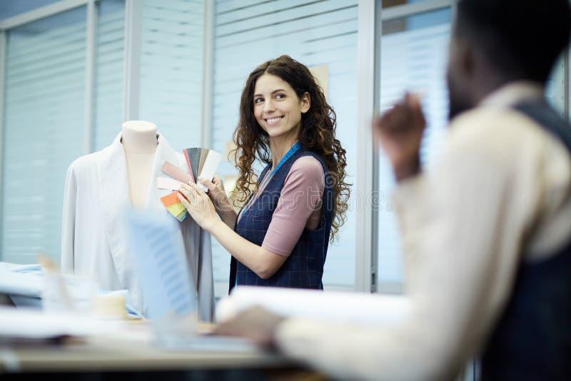 投入颜色样式的微笑的妇女对夹克显示设计师 免版税库存图片