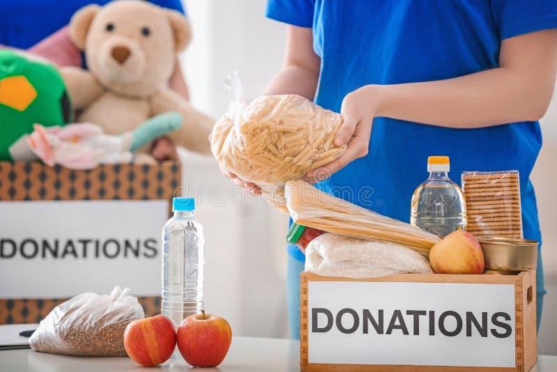 投入食品的女性志愿者在捐赠箱子 免版税图库摄影