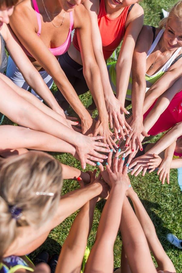 投入他们的秀丽的小组妇女一起递时髦的五颜六色的钉子艺术修指甲 免版税库存图片