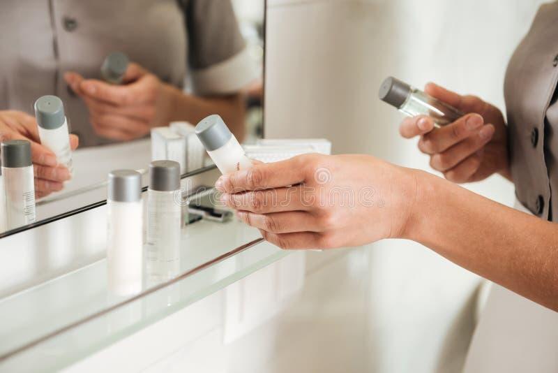 投入浴辅助部件的年轻旅馆佣人在卫生间 免版税库存照片
